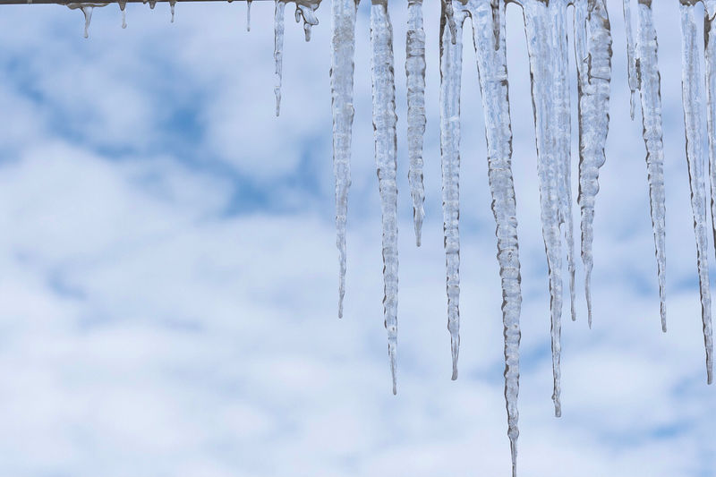 Low angle view of icicles hanging against sky