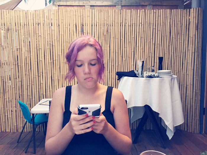 Woman Using Smart Phone While Sitting On Restaurant