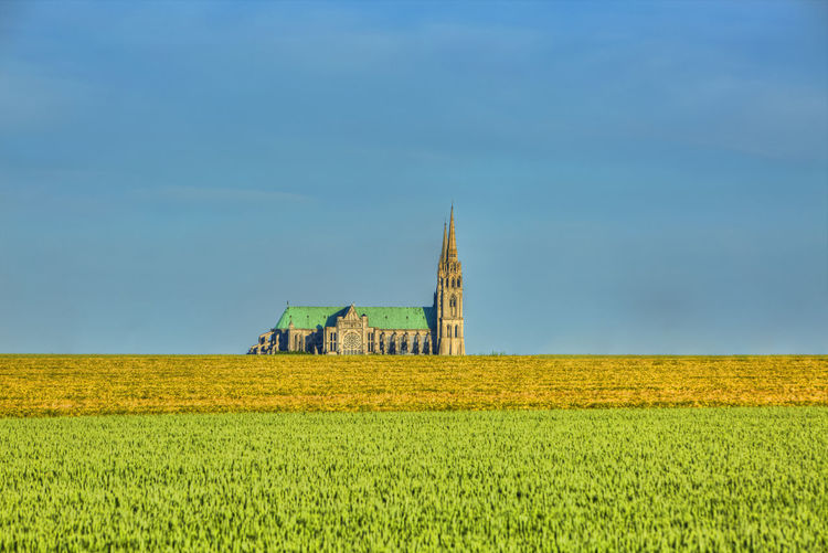 Image of the Cathedral of Our Lady of Chartres seen from outside of the city above the fields of cereals which surround the locality.This is a very famous Gothic cathedral which contains original stained glass from the 13th century. Sky Landscape Field Built Structure Land Architecture Plant Environment Building Exterior Building No People Nature Outdoors Cathedral Chartres Chartres, France Chartres Cathedral Field Cereals Summer Summertime Rural Scene Horizon Over Land Landmark Landmark Building France Beauce Agriculture Farm Scenics - Nature Green Color Religion