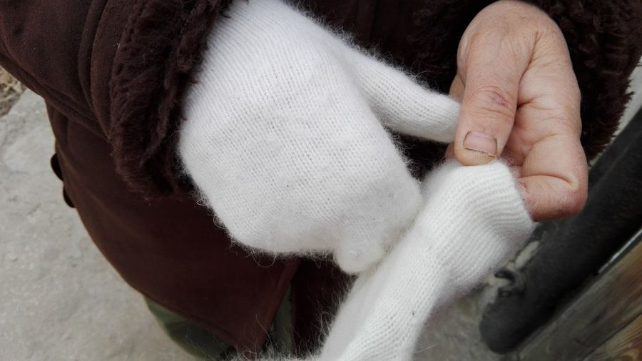 Close-up of human hand wearing knitted glove