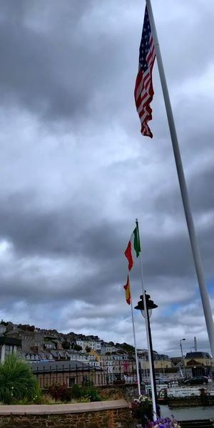 Low angle view of flags on building against sky