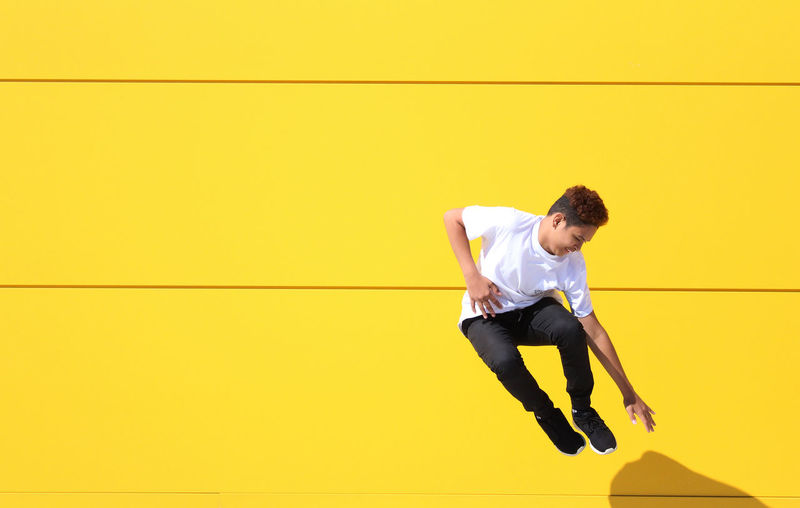 Full Length Of Teenage Boy Jumping By Yellow Wall