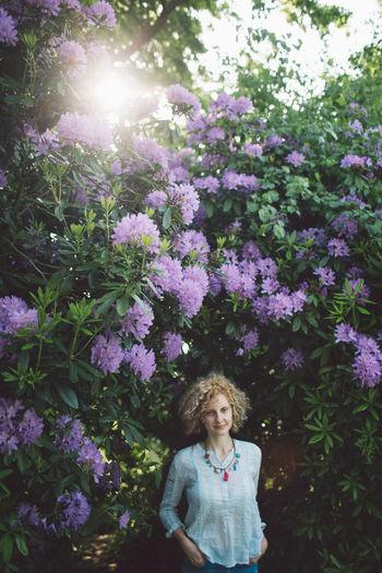 Portrait Of Smiling Mid Adult Woman Standing Against Purple Flowering Plants