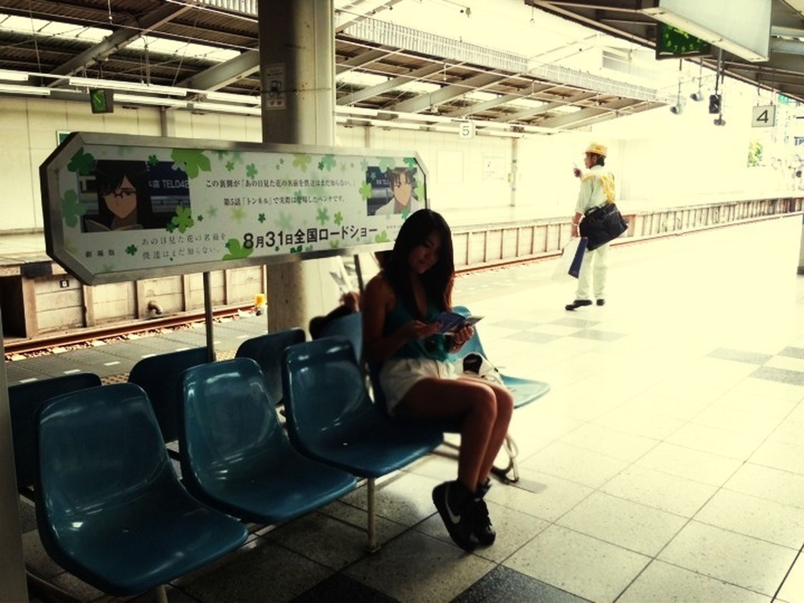 lifestyles, indoors, full length, communication, leisure activity, casual clothing, public transportation, transportation, railroad station platform, railroad station, travel, sitting, men, technology, passenger, text, standing, person