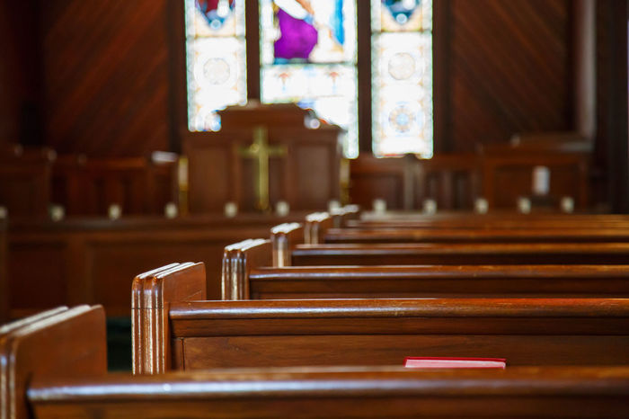 Stained glass windows in small church with wood pews Aisle Architecture Belief Bench Built Structure Courthouse Courtroom Focus On Foreground In A Row Indoors  Legal System Legal Trial No People Pew Place Of Worship Religion Seat Spirituality Wood - Material