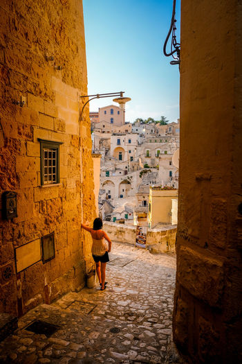 Rear view of woman and matera buildings