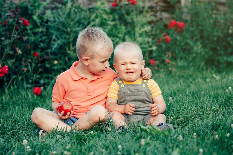 Full length of siblings sitting on grass