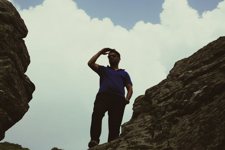 Low angle view of young man standing on cliff against sky