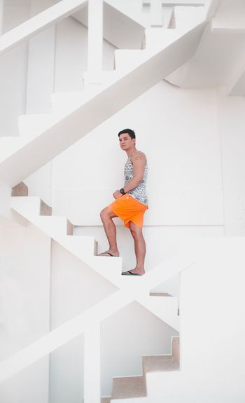 Low angle view of young woman on staircase at home