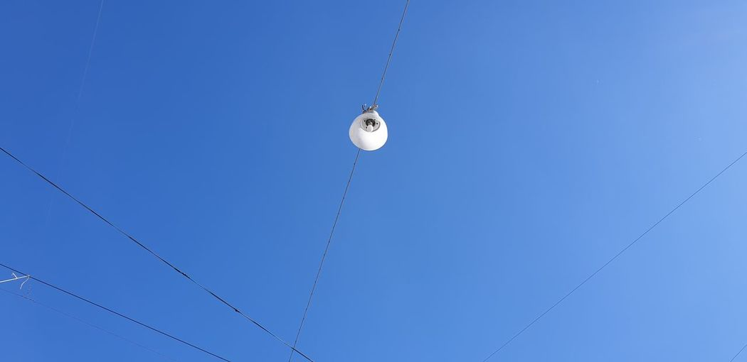 Low angle view of electric light against clear blue sky