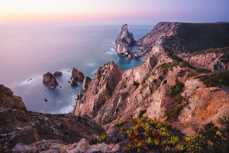 Panoramic view of rocks and sea against sky during sunset
