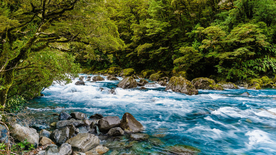 Scenic view of stream flowing through rocks in sea