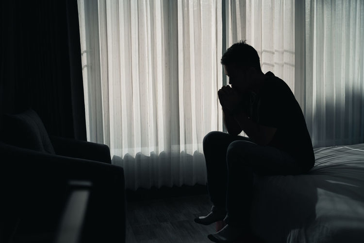 Silhouette man sitting against window at home