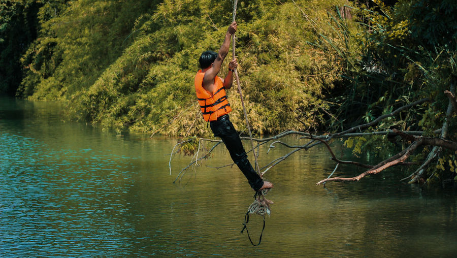 Side view full length of man swinging on rope over lake at forest