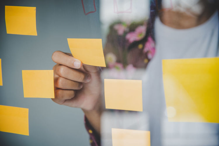 Midsection of businesswoman holding adhesive note on glass