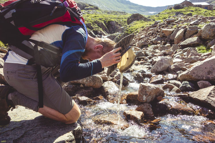 Water Dripping From Hat While Hiker Sitting By Stream