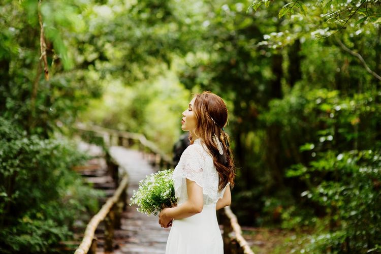 Side view of bride with eyes closed standing in forest