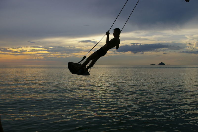 Silhouette man swinging above sea at sunset