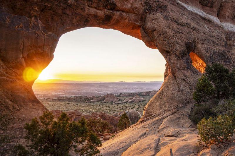 Rock formation on land against sky during sunrise