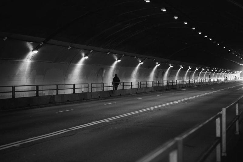 People walking on illuminated tunnel