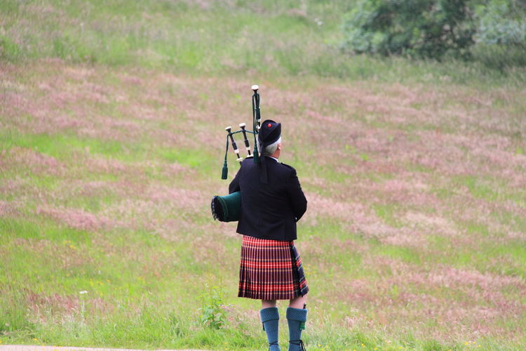 Rear View Of Bagpiper Standing On Grassy Field