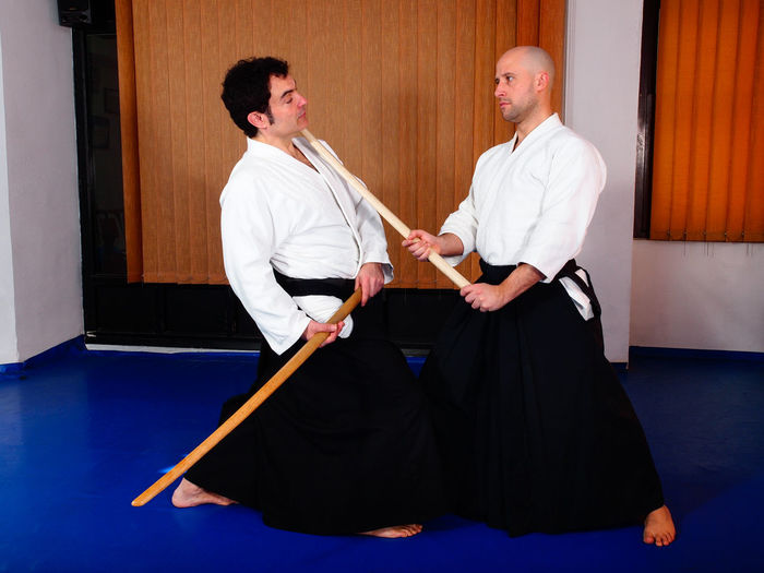 Men fighting with wooden swords on tatami mat