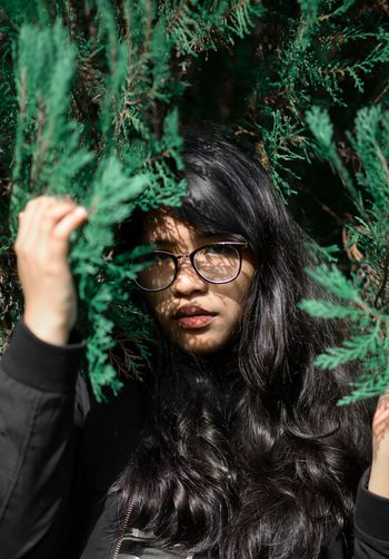 Portrait of young woman with long hair amidst plants