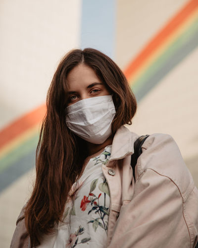 Portrait of beautiful young woman wearing a mask agaisnt buildings