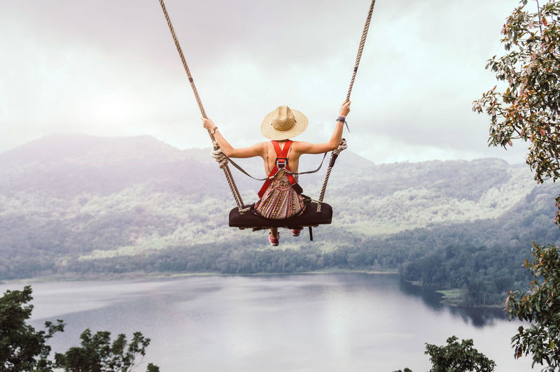 Rear view of woman sitting on swing over lake