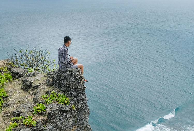 Side view of young man sitting on rock by sea