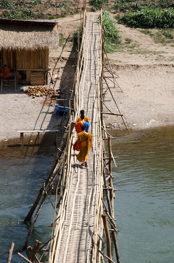 High angle view of monks working on footbridge over river