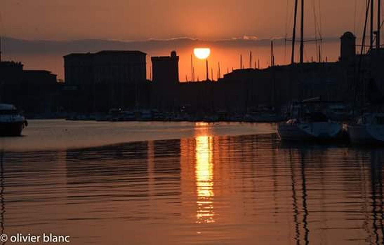 reflection, sunset, water, silhouette, sun, nautical vessel, travel destinations, city, illuminated, no people, outdoors, sky, building exterior, cityscape, tranquility, sea, harbor, moored, sailboat, yacht, architecture, nature, scenics, dawn, urban skyline, beauty in nature, sailing ship