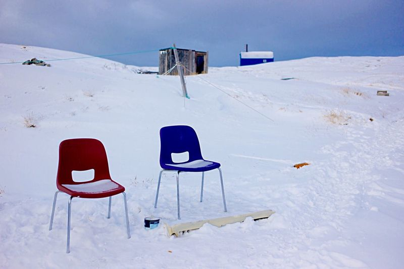 Empty Chairs On Snow Covered Field Against Sky