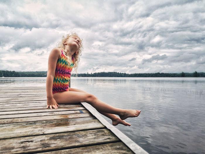 Full length of girl sitting on pier over lake against sky