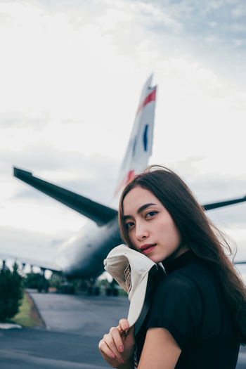 Portrait of beautiful young woman at airport against sky