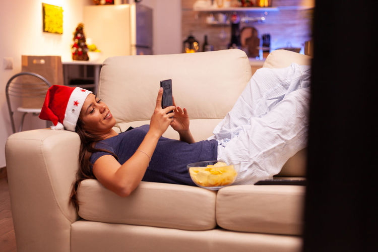 Midsection of woman using mobile phone while sitting on sofa at home