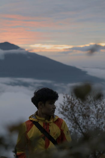 Portrait of boy on mountain against sky during sunset