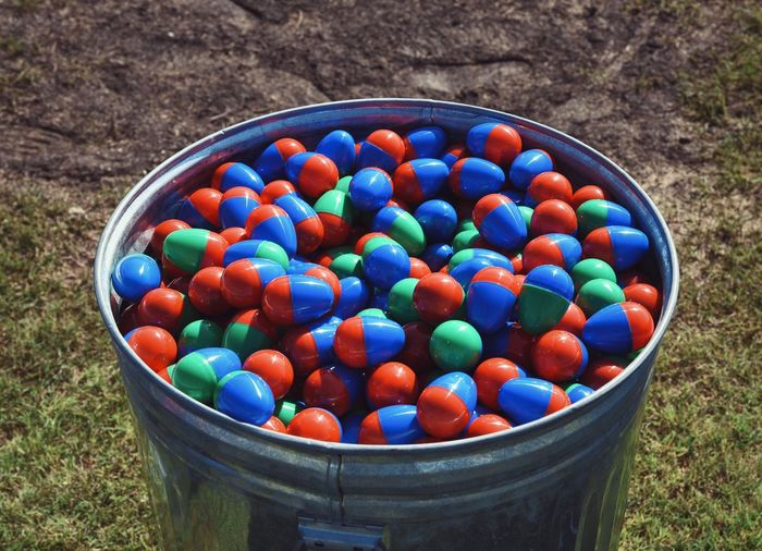 High Angle View Of Colorful Easter Eggs In Container On Field
