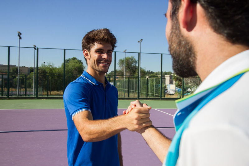 Male friends shaking hands while standing on tennis court