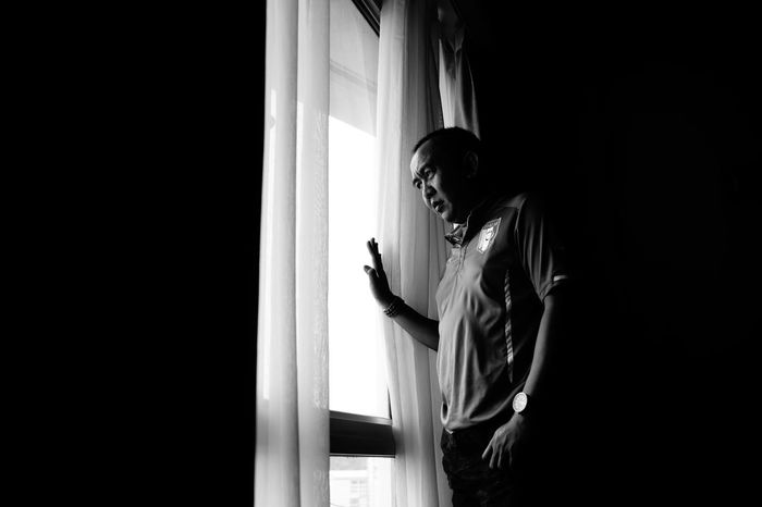 sad looking man looking outside. his face show his worries but his heart is full of joy because he know that he will be leaving soon. One Person Indoors  Adult Standing Real People Lifestyles Blackandwhite Blackandwhite Photography Travel Photography Sad Face Sad & Lonely Roomwithaview Room Portrait Light In The Darkness Face Expression Window Lonely Man Lonely Place  Hotel Room Monocrome Monocrome Black And White Art Is Everywhere TCPM Break The Mold