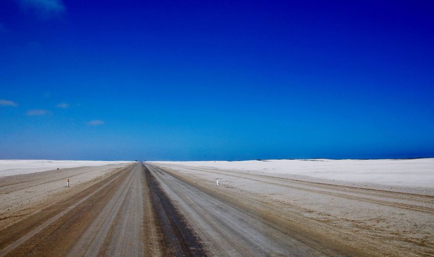 Road Amidst Land Against Clear Blue Sky