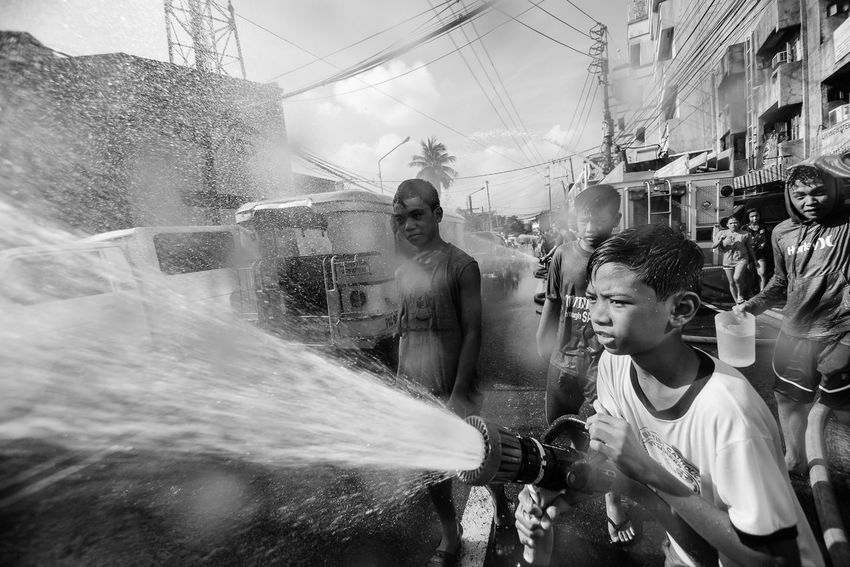 A boy sprays water with a frie hose to passersby in San Juan City in Metro Manila as they celebrate Whatta Whatta Festival on 24 June 2017. The festival commemorates the Feast of St. John The Baptist, who baptized Jesus Christ. | The Photojournalist - 2017 EyeEm Awards Black And White Philippines Larrymonseratepiojo EyeEm Philippines 👍 The Human Condition Everybodystreet EyeEm Best Shots Documentary Photography The Week On EyeEm People Water Lifestyles Child