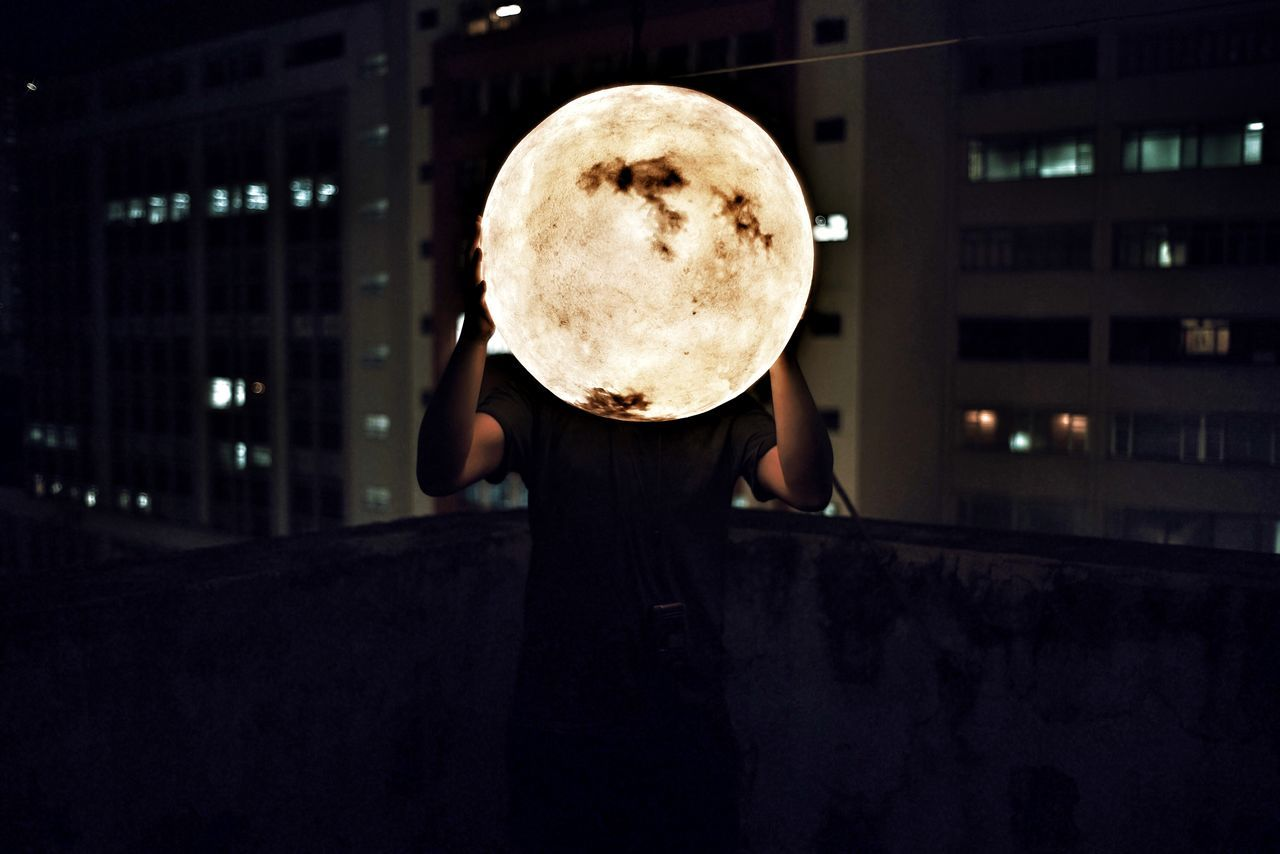 Man Holding Artificial Moon At Night