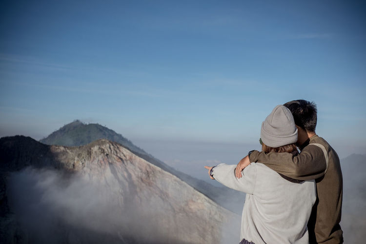 Rear View Of Couple Standing Looking At Mountain Against Sky