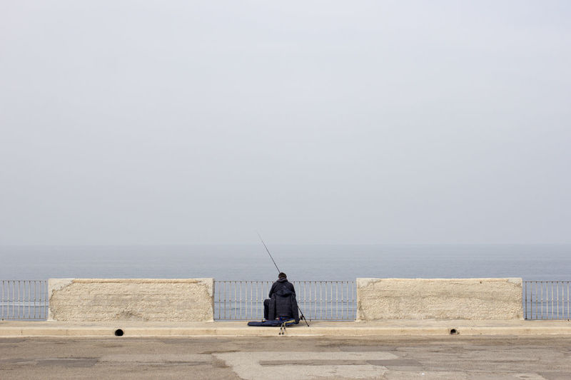 Rear view of person fishing at promenade against sky during foggy weather
