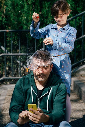 Girl splashing water over father head outdoors