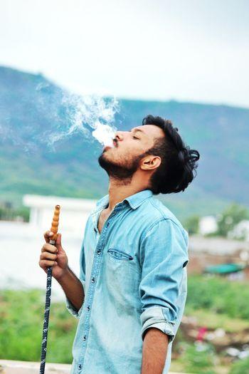 Young man smoking hookah against mountain