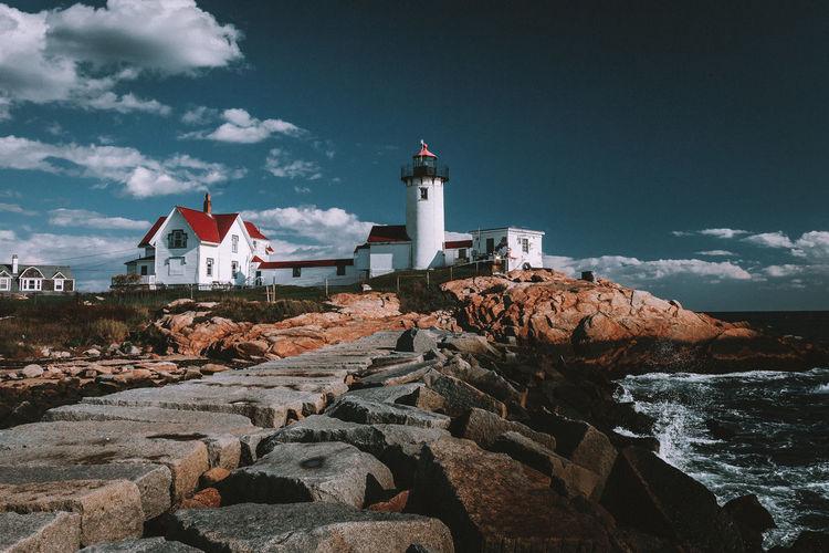 Lighthouse by buildings against sky
