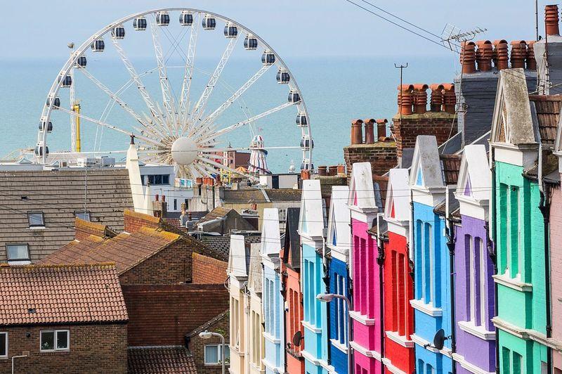 Ferris Wheel And Colorful Buildings Against Sea