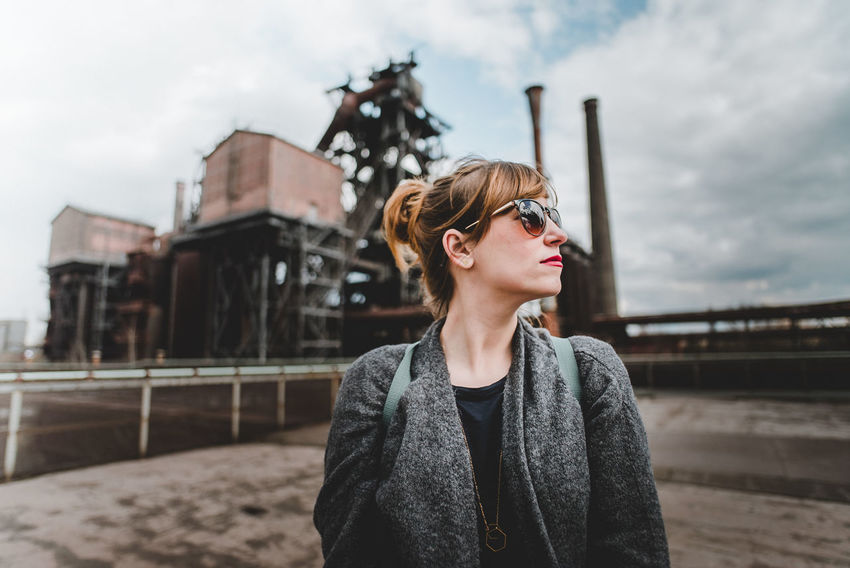 Industrial Girl Fashion Adult Architecture Beautiful Woman Beauty Building Exterior Built Structure Contemplation Fashion Fashion Photography Focus On Foreground Front View Glasses Hairstyle Leisure Activity Lifestyles Looking Away One Person Outdoors Real People Sky Standing Waist Up Young Adult Young Women